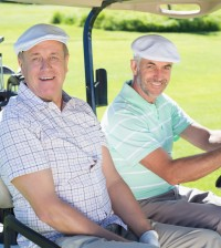 Golfing friends driving in their golf buggy smiling at camera on